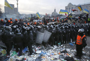 Photo - Pro-European Union activists wave flags as riot police pull back from Independence Square in Kiev, Ukraine, Wednesday, Dec. 11, 2013. Security forces clashed with protesters as they began tearing down opposition barricades and tents set up in the center of the Ukrainian capital early Wednesday, in an escalation of the weeks-long standoff threatening the leadership of President Viktor Yanukovych. (AP Photo/Sergei Grits)