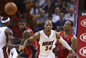 Photo - Miami Heat's Ray Allen (34) reacts after Toronto Raptors's DeMar DeRozan (10) knocked the ball from his hands during the second half of a NBA basketball game in Miami, Sunday, Jan. 5, 2014. The Heat won 102-97. (AP Photo/J Pat Carter)