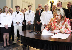 Photo - Oklahoma State University Center for Health Sciences medical students and staff watch as Gov. Mary Fallin signs a bill Wednesday that provides about $3 million to create residency programs at hospitals in rural, underserved areas.  Photo By Steve Gooch, The Oklahoman