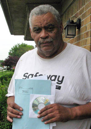 Photo - In this May 27, 2014 photo retired Detroit bus driver Art Vardiman holds a computer disk he received in the mail that holds hundreds of pages of documents, a six-page blue ballot about cuts to his pension and a white one on  health insurance in Detroit. Retirees with pensions at risk have until July 11 to vote on Detroit's exit plan from bankruptcy.  General retirees like Vardiman would see a 4.5 percent cut in their pension and elimination of annual inflation payments. Police and fire retirees fare better. (AP Photo/Ed White)