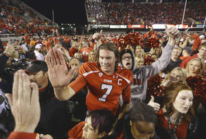 Photo - Utah quarterback Travis Wilson receives a high fives from a fan after Utah defeated Stanford 27-21 in Salt Lake City on Saturday. AP Photo