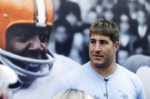 Photo - Cleveland Browns center Alex Mack talks with the media in front of a large mural of Hall of Fame running back Jim Brown at the NFL football team's facility in Berea, Ohio, Monday, April 14, 2014. The Pro Bowl center was one step out the door from leaving the Browns last week, but following a muddled free agency courtship, he's staying in Cleveland after the Browns matched the Jacksonville Jaguars contract offer. (AP Photo/Mark Duncan)