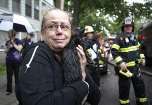 Photo - Cindy Piscopo holds her cat Zack after the cat was found by a firefighter after members of his battalion battled a blaze in a series of townhouses, including Piscopo's home in the Staten Island borough of New York, Thursday, June 5, 2014.  About 200 firefighters responded to the blaze that erupted at about 1 a.m. on the island south of Manhattan. They battled the five-alarm fire for several hours. A Fire Department of New York spokesman said 23 firefighters and 11 civilians suffered injuries ranging from minor to serious but none was considered life-threatening. He said the number was expected to climb slightly. (AP Photo/Kathy Willens)