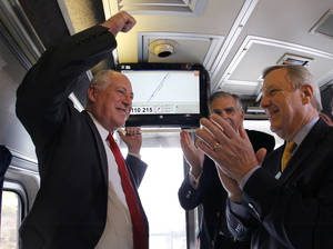 Photo -   Illinois Gov. Pat Quinn, left, U.S. Transportation Sec. Ray LaHood, center, and US Sen. Dick Durbin, D-Ill., celebrate after the Amtrak train they are riding reached 110 mph during a test run between Dwight and Pontiac, Ill., on Friday, Oct. 19, 2012, in Pontiac, Ill. (AP Photo/Charles Rex Arbogast)