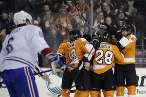 Photo - Philadelphia Flyers' Claude Giroux (28) celebrates with teammates after scoring during the second period of an NHL hockey game against the Montreal Canadiens, Thursday, Dec. 12, 2013, in Philadelphia. (AP Photo/Matt Slocum)