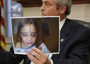 Photo - RANDY LACK / NO CONTEST PLEA: Pottawatomie County District Attorney Richard Smothermon holds up pictures of Serenity Deal as he speaks to the media in his office Shawnee., Okla. Friday, Nov. 9, 2012. Fired DHS workers Jennifer Shawn and Randy J. Lack pleaded no contest to misdemeanor suppression of evidence charges in the death of Serenity Deal. Photo by Bryan Terry, The Oklahoman