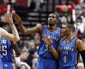 Photo - Oklahoma City Thunder's Kevin Durant, left, and Russell Westbrook celebrate with teammates during the second half of an NBA basketball game against the Portland Trail Blazers in Portland, Ore., Sunday, Jan. 13, 2013.  Durant score 33 points and Westbrook had 18 as they beat the Trail Blazers 87-83.(AP Photo/Don Ryan)