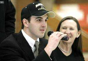 Photo - Tiny  Frantz, right, looks on at her son  Hunter  Frantz, signing to play for Army at West Point, during a signing ceremony at Putnam City North High School in Oklahoma City Wednesday, Feb. 4, 2009. BY PAUL B. SOUTHERLAND