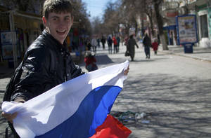 Photo - A local teenager waves with Russian flag in a street in Simferopol, Ukraine, on Monday, March 17, 2014. Ukraine's Crimean peninsula declared itself independent Monday after its residents voted overwhelmingly to secede and join Russia, while the United States and the European Union slapped sanctions against some of those who promoted the divisive referendum. (AP Photo/Ivan Sekretarev)