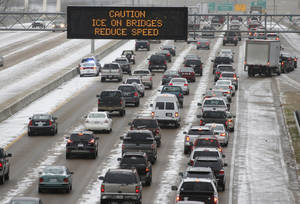 Photo - Traffic creeps along Interstate 55 in north Jackson, Miss., Tuesday, Jan. 28, 2014, as ice and snow flurries cause difficult driving conditions. A severe winter storm is expected to hit the state, bringing ice and snow to the Gulf Coast. (AP Photo/Rogelio V. Solis)