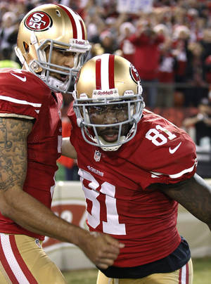 Photo - San Francisco 49ers wide receiver Anquan Boldin (81) celebrates with quarterback Colin Kaepernick (7) after scoring on a 10-yard touchdown reception against the Atlanta Falcons during the second half of an NFL football game in San Francisco, Monday, Dec. 23, 2013. (AP Photo/Tony Avelar)