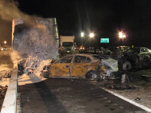 photo - A tractor-trailer still smolders hours after a chain-reaction crash on the Long Island Expressway on Wednesday, Dec. 19, 2012 in Shirley, N.Y. At least one person was killed and 32 others were injured in the pileup, which involved about two dozen vehicles. (AP Photo/Frank Eltman)