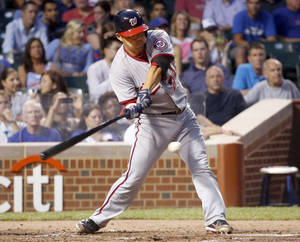 Photo - Washington Nationals' Kurt Suzuki hits a two-run single off Chicago Cubs starting pitcher Jake Arrieta during the second inning of a baseball game on Wednesday, Aug. 21, 2013, in Chicago. (AP Photo/Charles Rex Arbogast)
