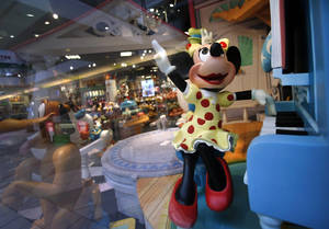 Photo - In this Friday, Jan. 31, 2014, photo, a Minnie Mouse character plays piano in a Disney Store display window in Saugus, Mass. Walt Disney Co. reports quarterly financial results after the market closes on Wednesday, Feb. 5, 2014. (AP Photo/Elise Amendola)