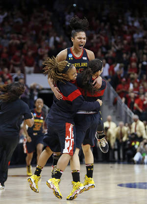 Photo - Maryland forward Alyssa Thomas, top,celebrates with guard Sequoia Austin, left, and another player after Maryland defeated Louisville 76-73 in a regional final of the NCAA women's college basketball tournament Tuesday, April 1, 2014, in Louisville, Ky. (AP Photo/John Bazemore)