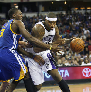 Photo - Sacramento Kings center DeMarcus Cousins, right, drives to the basket around Golden State Warriors defender Festus Ezeli during the second half of an NBA basketball game in Sacramento, Calif., on Wednesday, Dec. 19, 2012. The Kings won 131-127.(AP Photo/Steve Yeater)
