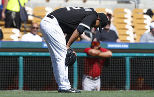 Photo - Chicago White Sox pitcher Jose Quintana reacts to being hit by a Arizona Diamondbacks Gerardo Parra hit in the first inning during an exhibition baseball game in Glendale, Ariz., Saturday, March 8, 2014. Quintana left the game after the play. (AP Photo/Paul Sancya)