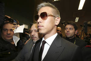 Photo - AC Milan's Keisuke Honda, of Japan, arrives at Milan's international airport Malpensa, Italy, Saturday, Jan. 4, 2014. New Milan signing Keisuke Honda likely won't play this weekend but could make his debut against Sassuolo a week later. (AP Photo/Antonio Calanni)