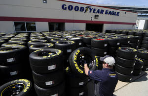 Photo - Brayden Wienke stacks tires at Texas Motor Speedway in Fort Worth, Texas, Friday, April 4, 2014. NASCAR will not regulate tire pressures at the speedway, and if drivers have tire failures during Sunday's race officials believe they will not be able to blame Goodyear. (AP Photo/Ralph Lauer)