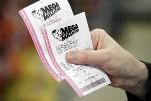 Photo - File photo - A customer at a convenience store holds her Mega Millions lottery tickets Friday, March 30, 2012, in Portland, Ore. (AP Photo/Rick Bowmer)