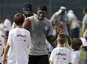 photo -   Jacksonville Jaguars rookie wide receiver Justin Blackmon greets kids at an NFL football Play 60 youth clinic at the Cleveland Browns training facility in Berea, Ohio Friday, June 29, 2012. (AP Photo/Mark Duncan)
