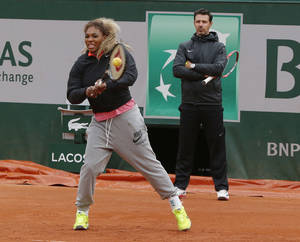 Photo - Serena Williams of the U.S., returns the ball while her coach Patrick Mouratoglou, right, looks on during a training session for the French Open tennis tournament, at the Roland Garros stadium in Paris, Saturday, May 24, 2014. The French Open tennis tournament starts Sunday. (AP Photo/Michel Euler)