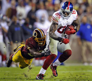 Photo - Washington Redskins inside linebacker London Fletcher reaches to stop New York Giants tight end Martellus Bennett (85) during the first half of an NFL football game in Landover, Md., Monday, Dec. 3, 2012. (AP Photo/Nick Wass)