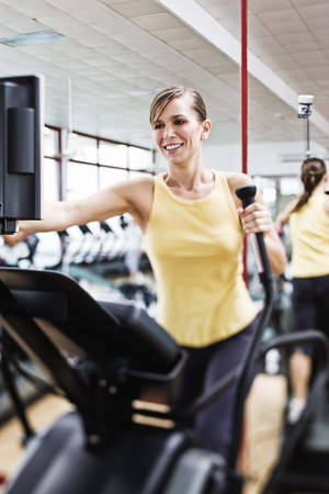 photo - Woman exercising on elliptical machine