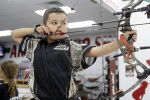 Photo - Archer Jackson Rhodes practices at the archery range at H&H Shooting Sports in Oklahoma City, OK, Thursday, July 18, 2013,  Photo by Paul Hellstern, The Oklahoman