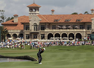 Photo -   Tiger Woods hits from the 18th fairway during the first round of the Players Championship golf tournament, Thursday, May 10, 2012, at TPC Sawgrass in Ponte Vedra Beach, Fla. (AP Photo/Chris O'Meara)