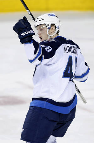 Photo - Winnipeg Jets' Carl Klingberg, from Sweden, celebrates his first NHL goal, against the Calgary Flames, during second period NHL action in Calgary, Alberta, Friday, April 11, 2014. (AP Photo/The Canadian Press, Larry MacDougal)