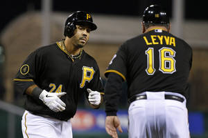 Photo - Pittsburgh Pirates' Pedro Alvarez (24) rounds third to greetings from coach Nick Leyva (16) after hitting a solo home run off St. Louis Cardinals starting pitcher Shelby Miller during the second inning of a baseball game in Pittsburgh on Friday, April 4, 2014. (AP Photo/Gene J. Puskar)