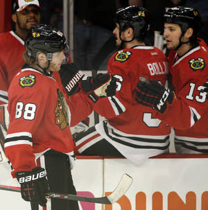 Photo - Chicago Blackhawks' Patrick Kane (88) celebrates with teammates after scoring a goal against the Detroit Red Wings during the first period of Game 2 of an NHL hockey Stanley Cup playoffs Western Conference semifinals Saturday, May 18, 2013, in Chicago. (AP Photo/Nam Y. Huh)