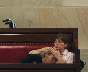 Photo - Rose Homuth of Cuba, N.Y., holds her son Brady Homuth, 25, in the Senate gallery at the Capitol as senators debate the medical marijuana bill on Friday, June 20, 2014, in Albany, N.Y. The Senate passed the bill making New York the 23rd state to legalize, but the drug won't be available for at least 18 months while regulations are written and five state-approved producers and distributors are chosen. Brady suffers from retractable seizure disorder. (AP Photo/Mike Groll)