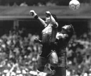 Photo - FILE - This is a Sunday, June 22, 1986 file photo of Argentina's Diego Maradona, left, as he is seen in the controversial action in which he knocked the ball with his left hand into the net of England's goalie Peter Shilton to score his team's first goal when Argentina defeated England 2-1 in the World Cup quarterfinal in the Mexico City Aztec stadium. Cheating. It's an ugly side of the beautiful game and it involves just about every aspect of it. The World Cup in Brazil begins in June and the founders of association football would shudder at how entrenched deception and trickery have become in the modern game. (AP Photo/El Grafico, File)