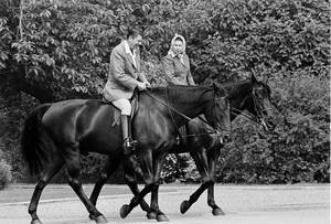 Photo - FILE - In this June 8, 1982 file photo, U.S. President Ronald Reagan, on Centennial, and Britain's Queen Elizabeth II, on Burmese, go horseback riding on the grounds of Windsor Castle, England. It is not often that the president of the United States needs to seek fashion advice. But when Ronald Reagan was getting ready for a visit to England as a guest of Queen Elizabeth II in June 1982, his people had an important question for the Brits: Just what does one wear to go riding with the queen in the magnificent horse country surrounding Windsor Castle? The answer: Something smart, but casual, of course. Riding boots, breeches and a turtleneck sweater would do fine _ no need for formal riding attire.  The fashion inquiry is but one tidbit contained in nearly 500 pages of formerly Confidential documents relating to the Reagan visit being made public Friday, Dec. 28, 2012 by Britain's National Archives. (AP Photo/Bob Daugherty, File)