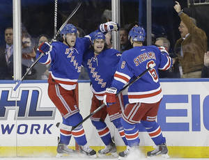 Photo - New York Rangers' Derick Brassard, left, and Anton Stralman, right, celebrate with Mats Zuccarello after Zuccarello scored a goal during the first period against the Philadelphia Flyers in Game 1 of an NHL hockey first-round playoff series on Thursday, April 17, 2014, in New York. (AP Photo/Frank Franklin II)