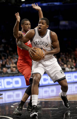 Photo - Brooklyn Nets' Joe Johnson, right, looks for the basket past Philadelphia 76ers' Thaddeus Young during the first half of an NBA basketball game at the Barclays Center, Monday, Dec. 16, 2013, in New York. (AP Photo/Seth Wenig)