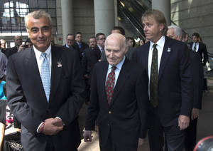 Photo - Milwaukee Bucks owner Herb Kohl walks into a news conference after reaching a deal to sell the franchise to New York investment firm executives Marc Lasry, right, and Wesley Edens, left, Wednesday, April 16, 2014, in Milwaukee. (AP Photo/Morry Gash)
