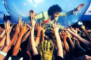 Right: Wayne Coyne surfs the crowd in his famous space bubble. PHOTO PROVIDED