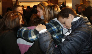 photo - Girls embraces outside St. Rose of Lima Roman Catholic Church, which was filled to capacity, during a healing service held in for victims of an elementary school shooting in Newtown, Conn., Friday, Dec. 14, 2012. A gunman opened fire at Sandy Hook Elementary School in Newtown, killing 26 people, including 20 children. (AP Photo/Charles Krupa)