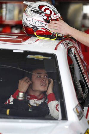 Photo - Kyle Larson waits in his car during practice for Saturday's NASCAR Sprint Cup series auto race at Charlotte Motor Speedway in Concord, N.C., Thursday, Oct. 10, 2013. (AP Photo/Terry Renna)