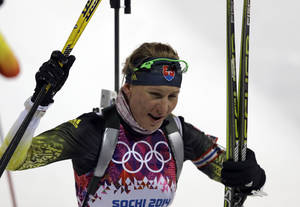 Photo - Slovakia's Anastasiya Kuzmina smiles after completing the women's biathlon 7.5k sprint, at the 2014 Winter Olympics, Sunday, Feb. 9, 2014, in Krasnaya Polyana, Russia. (AP Photo/Kirsty Wigglesworth)