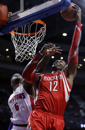 Photo - Houston Rockets center Dwight Howard (12) takes a shot against Detroit Pistons forward Josh Smith (6) during the first half of an NBA basketball game Saturday, Dec. 21, 2013, in Auburn Hills, Mich. (AP Photo/Duane Burleson)