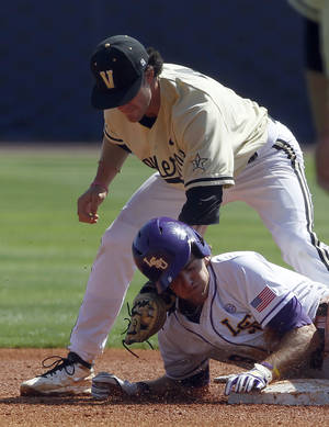 Photo - LSU's Mark Laird (9) beats the tag from Vanderbilt's Dansby Swanson (7) as he slides into second base during the first inning at the Southeastern Conference NCAA college baseball tournament on Wednesday, May 21, 2014, in Hoover, Ala. (AP Photo/Butch Dill)