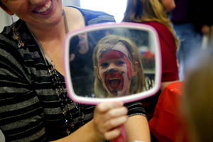 Photo - Daniella Shobert, 4, laughs as she sees her painted face.
