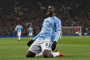 Photo - Manchester City's Yaya Toure celebrates after scoring against Manchester United during their English Premier League soccer match at Old Trafford Stadium, Manchester, England, Tuesday, March 25, 2014. (AP Photo/Jon Super)