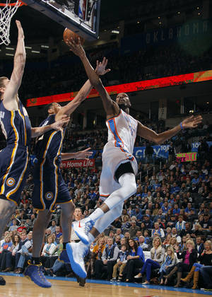 photo - Oklahoma City's Kevin Durant (35) shoots a lay up as Indiana's Tyler Hansbrough (50) and Gerald Green (25) defend during the NBA game between the Indiana Pacers and the Oklahoma City Thunder at the Chesapeake Energy Arena   Sunday,Dec. 9, 2012. Photo by Sarah Phipps, The Oklahoman