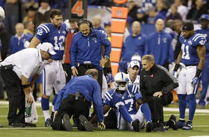 Photo - Indianapolis Colts wide receiver Reggie Wayne (87) talks to trainers as he injures his knee during the second half of an NFL football game, Sunday, Oct. 20, 2013, in Indianapolis. (AP Photo/Michael Conroy)