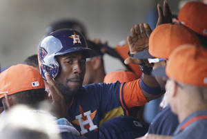 Photo - Houston Astros center fielder Dexter Fowler is congratulated in the dugout after scoring from third on a sacrifice fly by teammate Marc Krauss during the fourth inning of a spring exhibition baseball game in Kissimmee, Fla., Saturday, March 22, 2014. (AP Photo/Carlos Osorio)